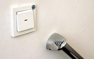 HYSYST-Siegel für sichtbare Hygiene im Krankenhaus an einem Lichtschalter und Haltegriff.